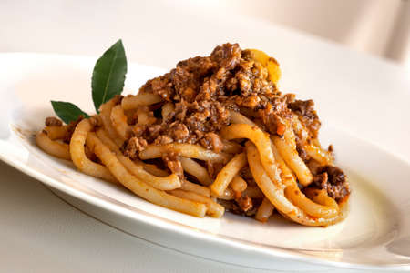 Dish of pici with wild boar ragout with bay leaves in white plate