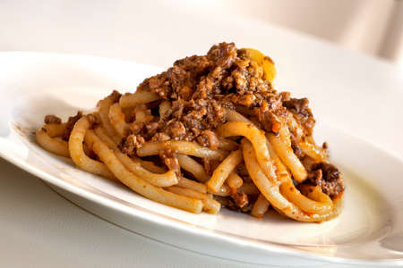 Dish of pici with wild boar ragout in white plate