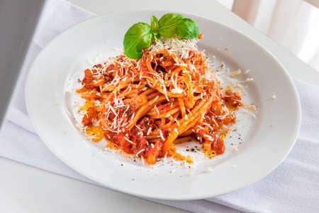 Plate of spaghetti pasta with tomato and pork cheek and pecorino cheese and basil 写真素材