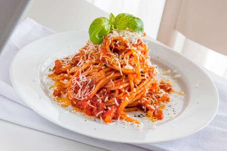 Plate of spaghetti pasta with tomato and pork cheek and pecorino cheese and basil 写真素材 - 166126596