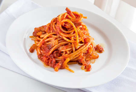 Plate of spaghetti pasta with tomato and pork cheek