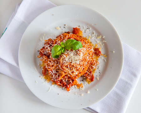 Top view of Plate of spaghetti pasta with tomato and pork cheek and pecorino cheese and basil 写真素材