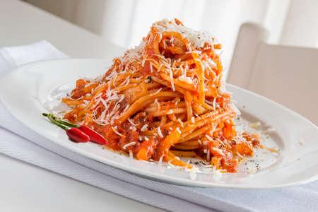 Plate of spaghetti pasta with tomato and pork cheek and pecorino cheese
