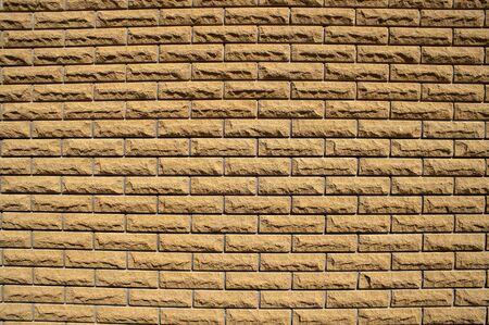 consisting: the wall consisting of small light brown bricks