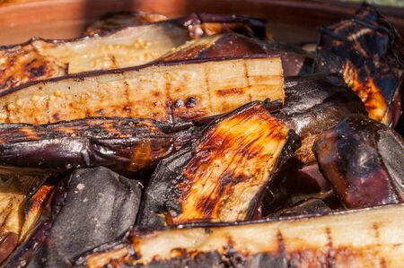 thoroughly: In length the eggplants cut by slices were fried thoroughly well on pieces of coal