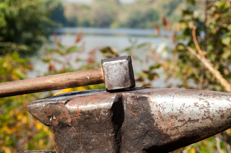 forger: medieval historical anvil and hammer at the festival reconstruction
