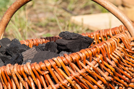 yard stick: charcoal lying in a wicker basket on a sunny day Stock Photo