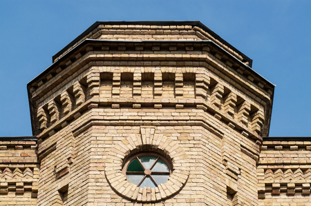round window: round window in a brick building on a sunny day