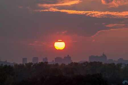 urban decline: the sun at sunset with clouds over the city and trees Stock Photo