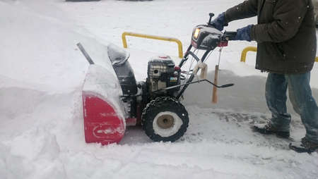 A man cleaning snow with snowblower