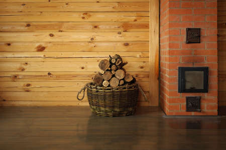 round oak firewood stacked in the basket near the stove Stock Photo
