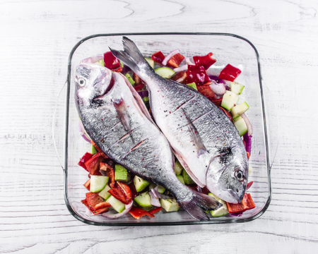 gilthead: Gilt-head breams and vegetables in a glass bakeware.