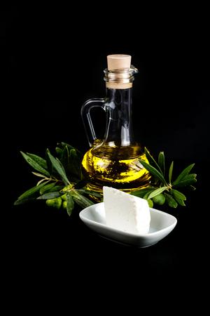 queso blanco: Botella de aceite de oliva, rama de olivo y queso blanco sobre negro.
