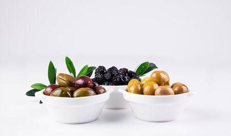 rama de olivo: Aceitunas en cuencos aislados en blanco rama, de oliva en el fondo. Foto de archivo