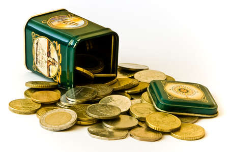 Various coins in a green tin Stock Photo