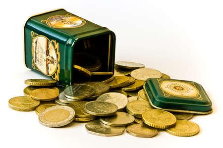 Various coins in a green tin Stock Photo