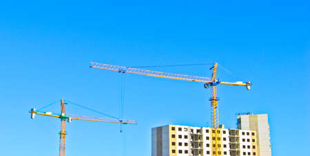 Large building cranes above the unfinished apartment house.