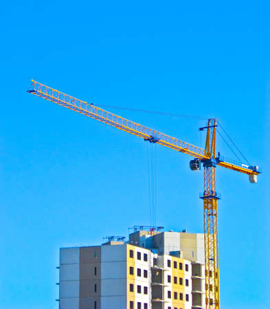 Unfinished apartment with large building crane at the sky background.