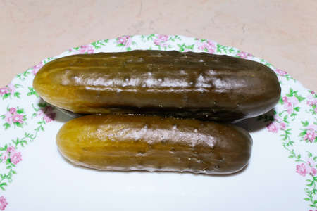 Traditional Russian snack - marinated cucumbers served on the plate