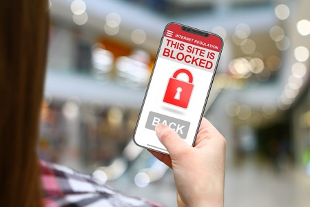 Site blocked concept, girl with frameless phone on blurred mall background Stock Photo
