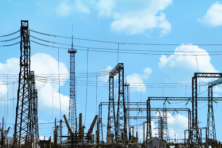 High voltage electric power station - electric poles and lines on blue sky background