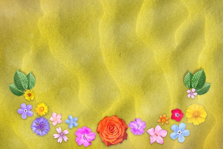 Beautiful decoration flowers frame with empty in center on yellow sand background.
