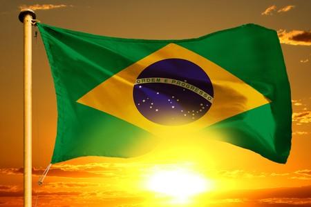 Brazil flag weaving on the beautiful orange sunset background