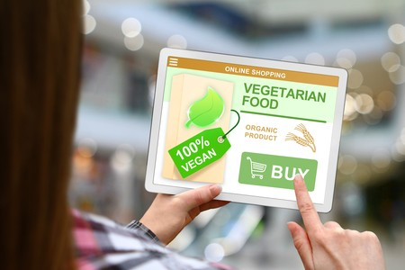 Vegetarian food concept, girl with tablet pc on blurred mall background Stock Photo