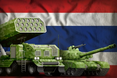 tank and rocket artillery with summer pixel camouflage on the Thailand flag background. Thailand heavy military armored vehicles concept. 3d Illustration