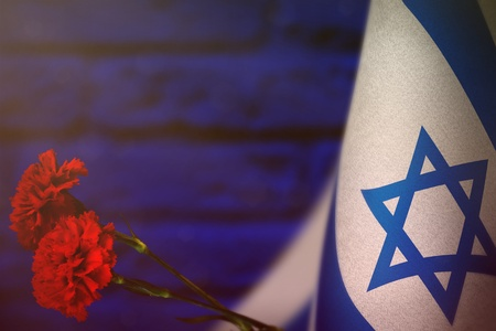 Israel flag with two red carnation flowers for honour of veterans or memorial day on blue blurred painted brick wall.