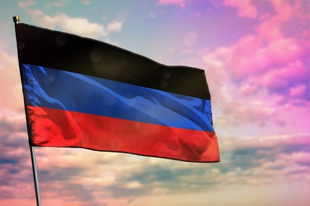 Fluttering Donetsk Peoples Republic flag on colorful cloudy sky background. Donetsk Peoples Republic prospering concept.