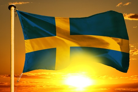 Sweden flag weaving on the beautiful orange sunset background Stockfoto