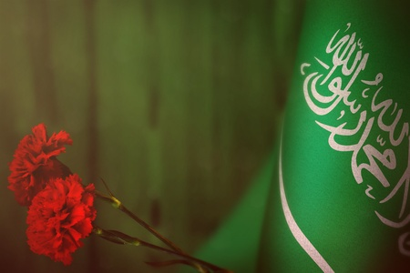Saudi Arabia flag with two red carnation flowers for honour of veterans day or memorial day on green blurred natural wood wall background. Saudi Arabia glory to the heroes of war concept.