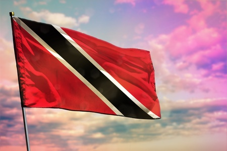 Fluttering Trinidad and Tobago national flag on colorful cloudy sky background. Trinidad and Tobago prospering concept.