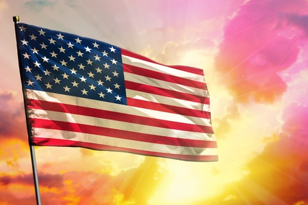 Fluttering USA flag on beautiful colorful sunset or sunrise background. USA success or happiness concept. Фото со стока
