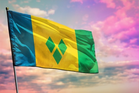 Fluttering Saint Vincent and the Grenadines flag on colorful cloudy sky background. Saint Vincent and the Grenadines prospering concept.