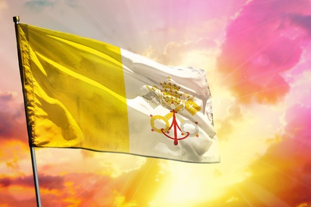 Fluttering Holy See flag on beautiful colorful sunset or sunrise background. Holy See success and happiness concept.