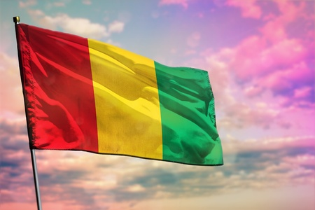 Fluttering Guinea flag on colorful cloudy sky background. Guinea prospering concept. Imagens