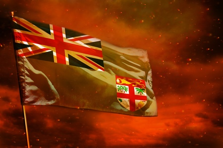 Fluttering Fiji flag on crimson red sky with smoke pillars background. Fiji problems concept.