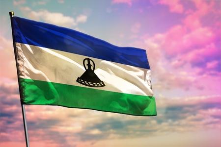 Fluttering Lesotho flag on colorful cloudy sky background. Lesotho prospering concept. Stock fotó