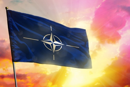 Fluttering NATO flag on beautiful colorful sunset or sunrise background. NATO success and happiness concept.