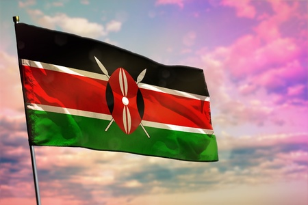 Fluttering Kenya flag on colorful cloudy sky background. Kenya prospering concept.