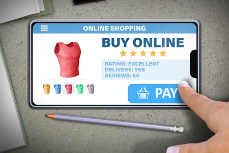 online shopping technology concept - hand with mobile phone tapping the button pay on stone table background