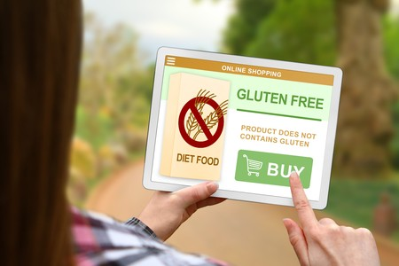 Gluten free diet concept, girl with tablet pc on blurred nature background