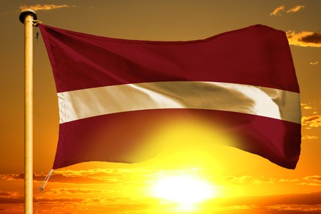 Latvia flag weaving on the beautiful orange sunset background