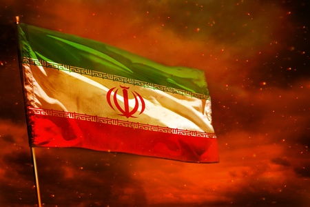 Fluttering Iran flag on crimson red sky with smoke pillars background. Iran problems concept.
