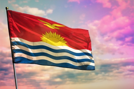 Fluttering Kiribati flag on colorful cloudy sky background. Kiribati prospering concept.