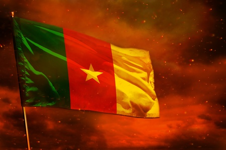 Fluttering Cameroon flag on crimson red sky with smoke pillars background. Cameroon problems concept.
