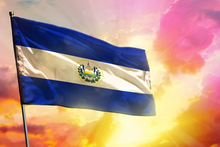Fluttering El Salvador flag on beautiful colorful sunset or sunrise background. El Salvador success and happiness concept.