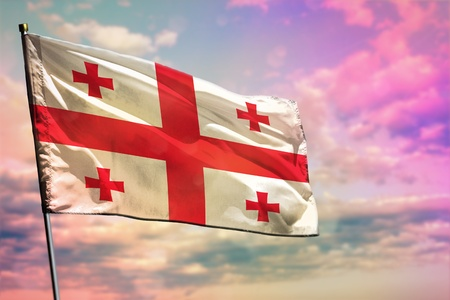 Fluttering Georgia flag on colorful cloudy sky background. Georgia prospering concept. Фото со стока